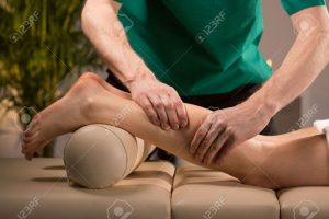 Massage Therapist Kneading a Patient's Calf